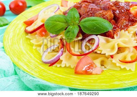 Pasta Farfalle with chicken tomato blue onion sweet pepper and tomato sauce on a plate on a bright wooden background. A traditional Italian dish. Close up.