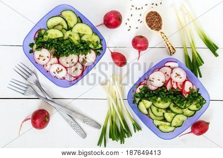 A light vitamin spring - summer salad with fresh cucumbers radish and green onions with oil and flax seeds in bowls on a white wooden background. Top view. Dietary vegan dish. Healthy diet.