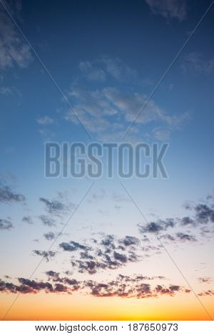 Beautiful blue sky in sunset colors with sparse clouds