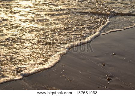 sunrise and breaking waves with white water on the beach early in the morning