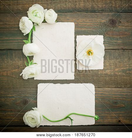 Paper cards and envelope with white flowers on wooden background. Flat lay, top view. Vintage background.