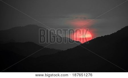 Long shot of African sunset with red sun and mountain range