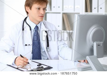 Friendly male doctor is sitting at the table and working in the hospital office. Ready to examine and help patients. High level and quality medical service concept