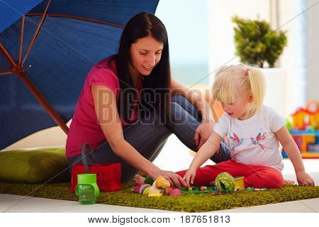Mother And Daughter Playing Together, Sunny Outdoors