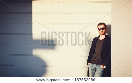 Stylish handsome man is posing next to wall. Copy space