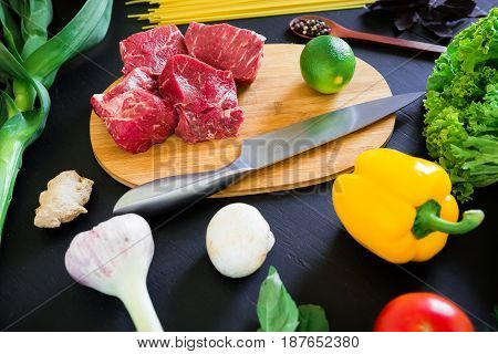Raw meat on cook board, knife, pasta and fresh vegetables on dark table. Top view. Flat lay. Food background