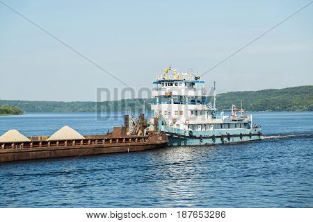 Cargo ship barge loaded with sand on the river