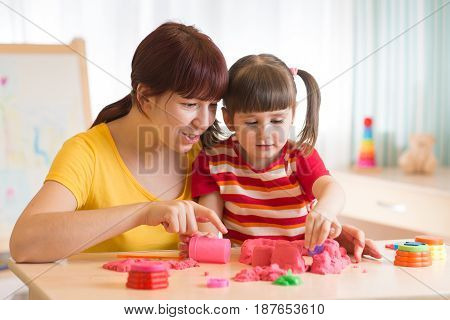 Child with therapist playing with toy the sand. Psychologist works sand therapy.