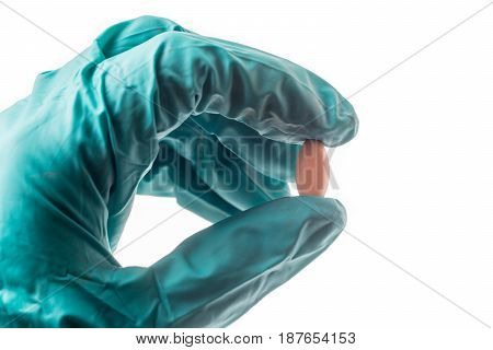 Hand with green protective glove holding an oblong pill isolated on white background