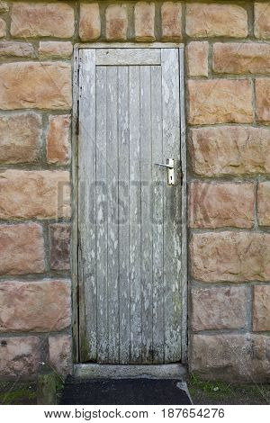 Old wooden door with peeling paint in a stone outside building
