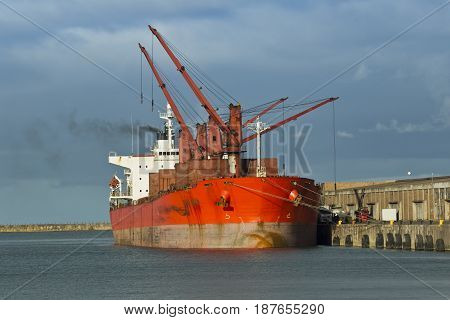 Loading of a cargo ship in a harbor while the engines are running and