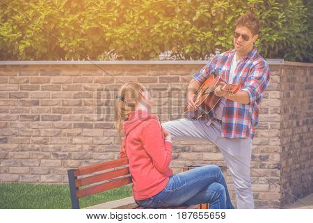 Romantic man singing song and playing guitar to his girlfriend in the park