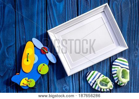 baby toys and shoes for baby shower design on blue wooden background top view mock-up