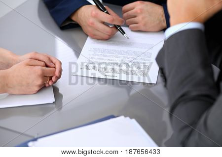 Business man is going to sign contract. Group of business people at meeting .