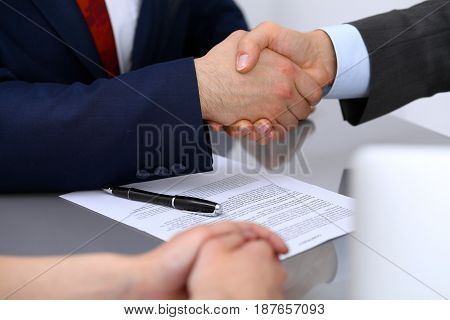 Two business man shaking hands to each other above signed contract.