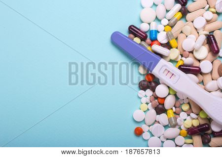Artificial insemination with pills. Tablets from pregnancy. A positive pregnancy test and pills on a mint background. Empty place for text.