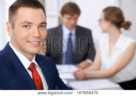 Portrait of cheerful smiling business man against a group of business people at a meeting