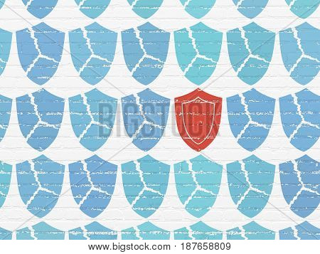 Protection concept: rows of Painted blue broken shield icons around red shield icon on White Brick wall background