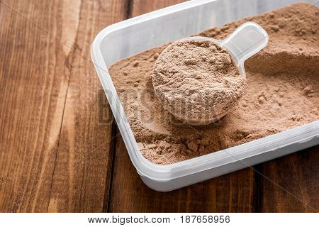 Fitness nutrition with scoop on wooden table background