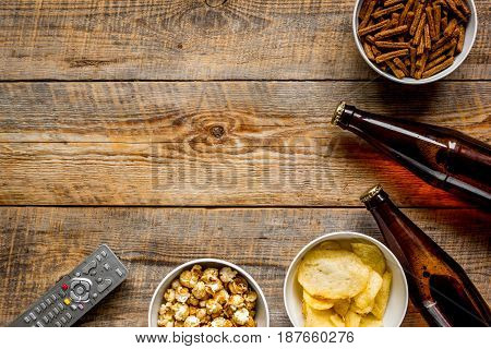 watching TV set with chips, beer and remote control on wooden background top view mock up