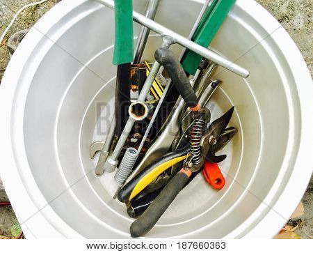 Hand Tools Collection of Used Wrench Pliers Pruning Shears in A White Bucket.