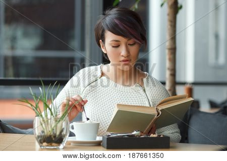 Young elegant woman sitting at table stirring up coffee with spoon and reading book in cafe.