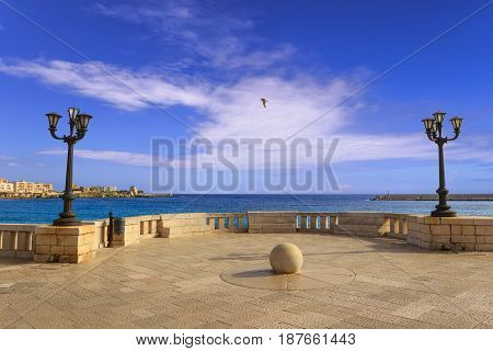 Salento coast: Coastal promenade of Otranto town: view of the port . Gull in flight between the lampposts. Italy (Apulia). poster