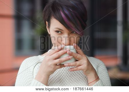 Young Asian woman in white sweater drinking coffee and looking away.
