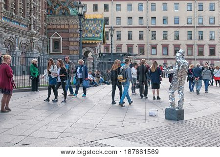 SAINT - PETERSBURG, RUSSIA - MAY 18, 2017: People pass by the street actor near The Church of the Resurrection (Savior on the Spilled Blood)