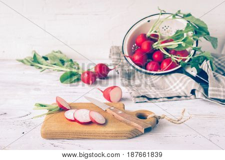 Fresh radishes sliced on the kitchen table. Light wooden background. Selective focus