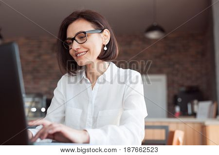 Adult woman in glasses and formal shirt sitting at table and browsing laptop.