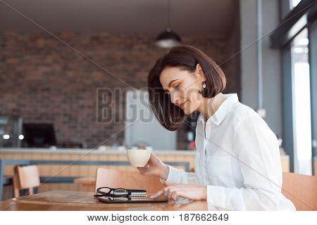 Side view of woman in white shirt sitting at table holding mug with coffee and browsing tablet.