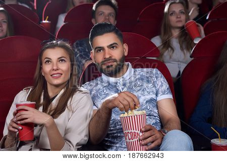 Two friends sitting in comfortable chairs in modern cinema hall, watching interesting movie and eating tasty popcorn.Young couple of arabian man with bread and caucasian woman spending time in cinema.
