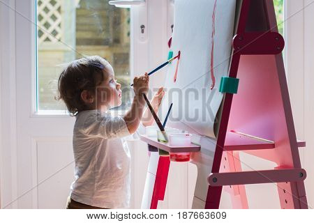 Little Girl Painting On The Easel