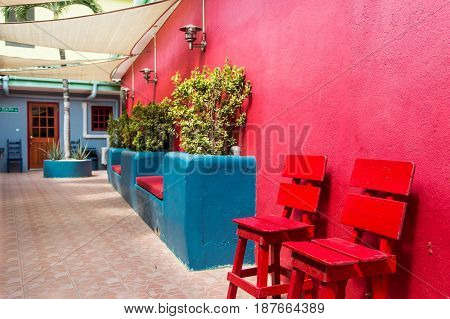 Red Wall Red Chairs and Blue Planter