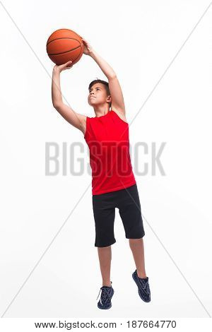 Confident young teen playing basketball preparing to throw a ball.