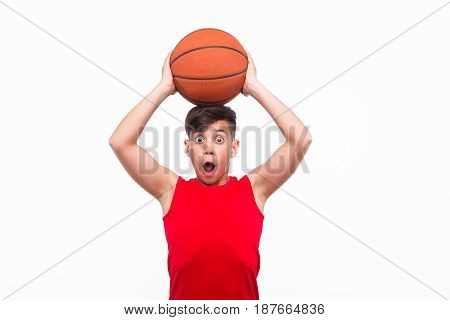 Shocked male teen looking at camera posing with basket ball.