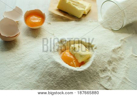 Preparation of ingredients for baking. Eggs flour milk sugar oil on a white wooden table.