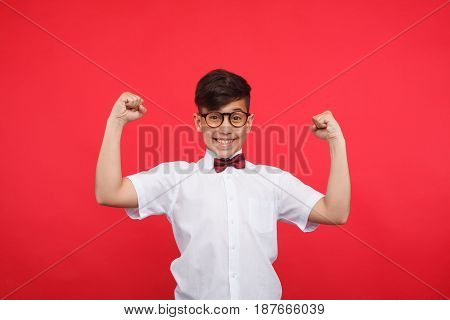Cheerful young boy wearing white shirt holding hands up and looking at camera.