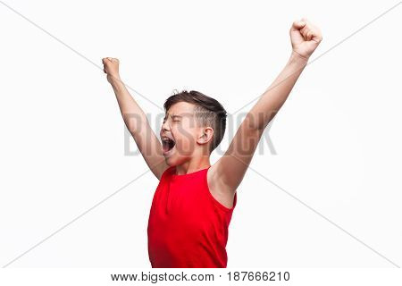 Young boy dressed in red t-shirt screaming happily with eyes closed and hands up isolated on white.