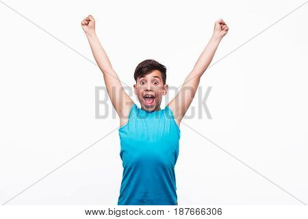 Cheerful excited teen boy looking at camera and screaming with hand up isolated on white.