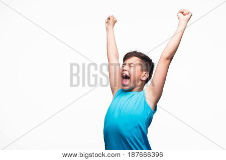 Excited young boy yelling with eyes closed and hands up isolated on white.