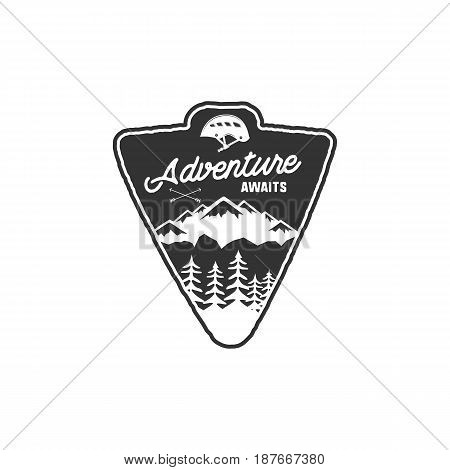 Hand drawn vintage camping badge and hiking label with mountains, forest, climb helmet and typography design. Quote text- Adventure awaits. Old style patch. Rustic stamp vector template.