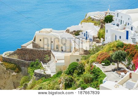 White town on the blossoming steep coast of the Greek island of Santorini on blue sea background