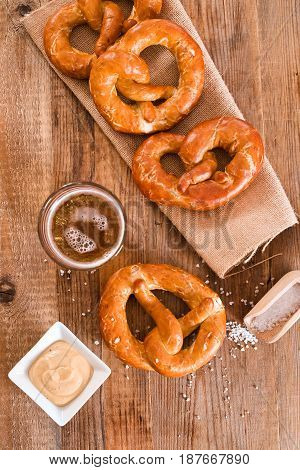Bavarian pretzels with beer glass on wooden table.