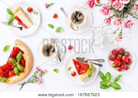 Coffee, delicious homemade strawberry cheesecake and flowers over white. Top view, flat lay.