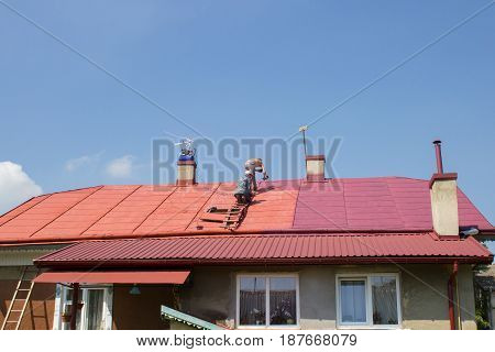 summer two men painted red roof compressor