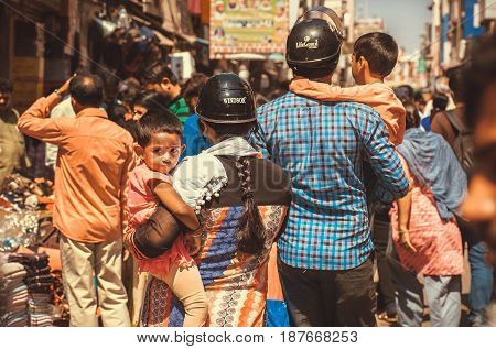 BANGALORE, INDIA - FEB 14, 2017: Unidentified boys in arms of parents in noisy crowd of the asian street on February 14, 2017. With population 8.52 million Bangalore is the third most populous indian city