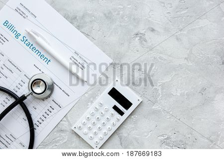 stethoscope, billing statement for doctor's work in medical center on stone background top view space for text