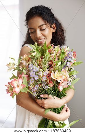 Portrait of young beautiful tender african girl in white dress smiling holding bouquet of flowers. Closed eyes.